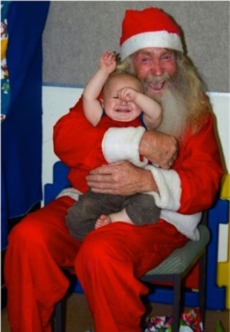 This is a scary man dressed like Santa clutching a panicked baby.